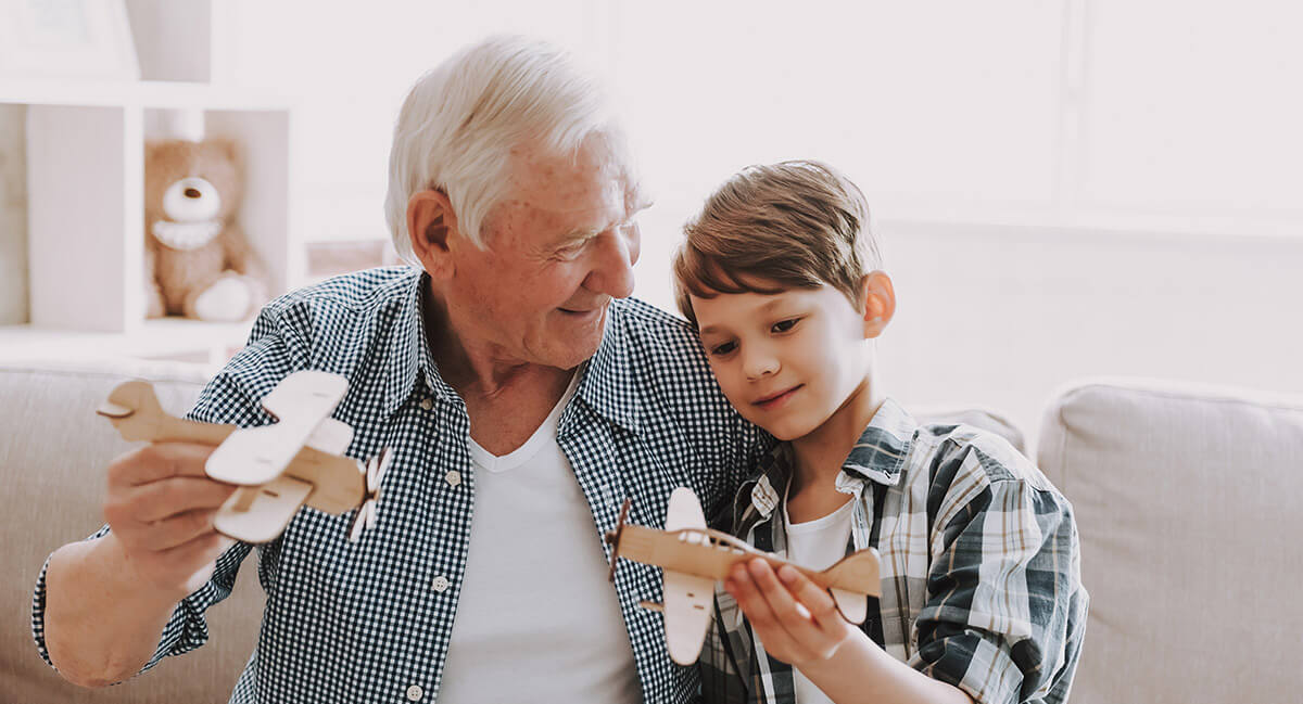 Smiling grandfather and grandson sitting on a sofa playing with wooden toy planes