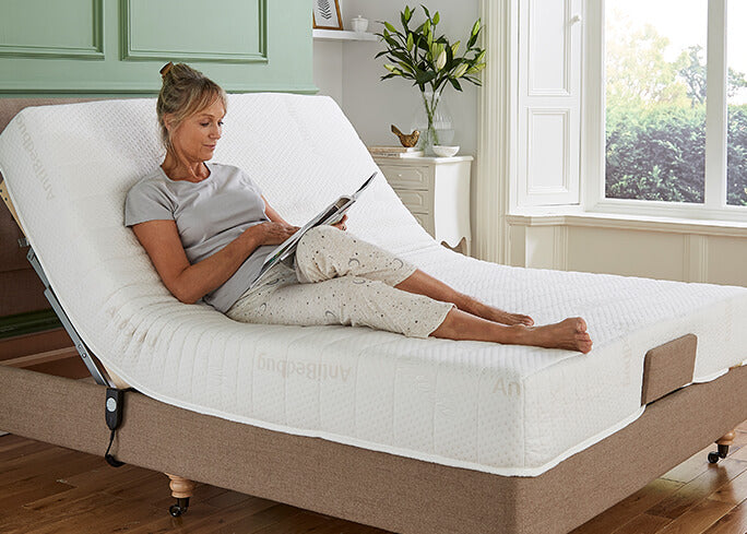 Woman sitting up in adjustable bed reading a magazine