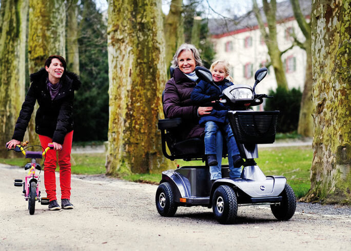 Grandmother riding mobility scooter with child on her knees. Mother is in the background smiling.