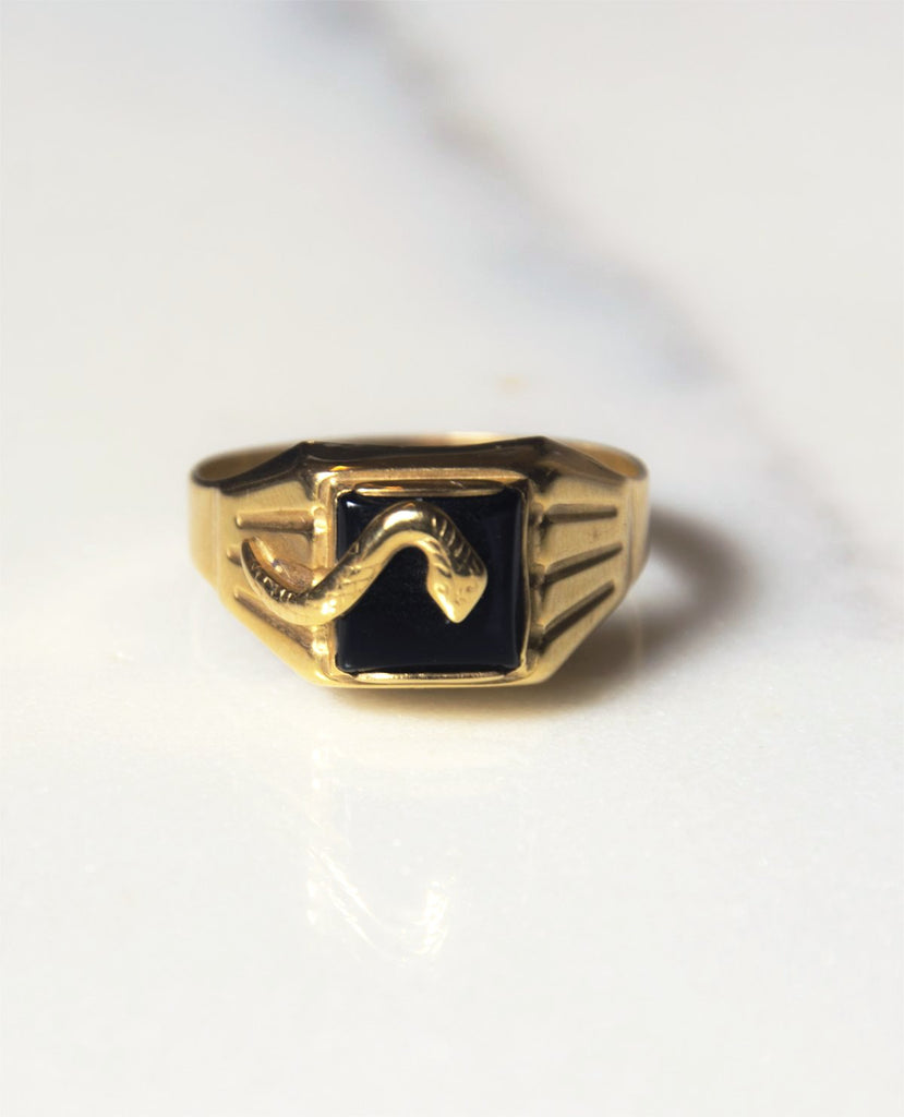 "18k gold ring dating from the mid 1970s with a square black onyx cabochon and a serpent head laying atop.  Originally a mens ring, the piece is hallmarked. There are several marks on the interior of the ring, the first of which features a capital ""McDz"" for an Italian goldsmith in Arezzo, Italy after 1972.  This is followed by the number ""750"" inside the image of a scale for 18k gold and AR for Arrezzo."