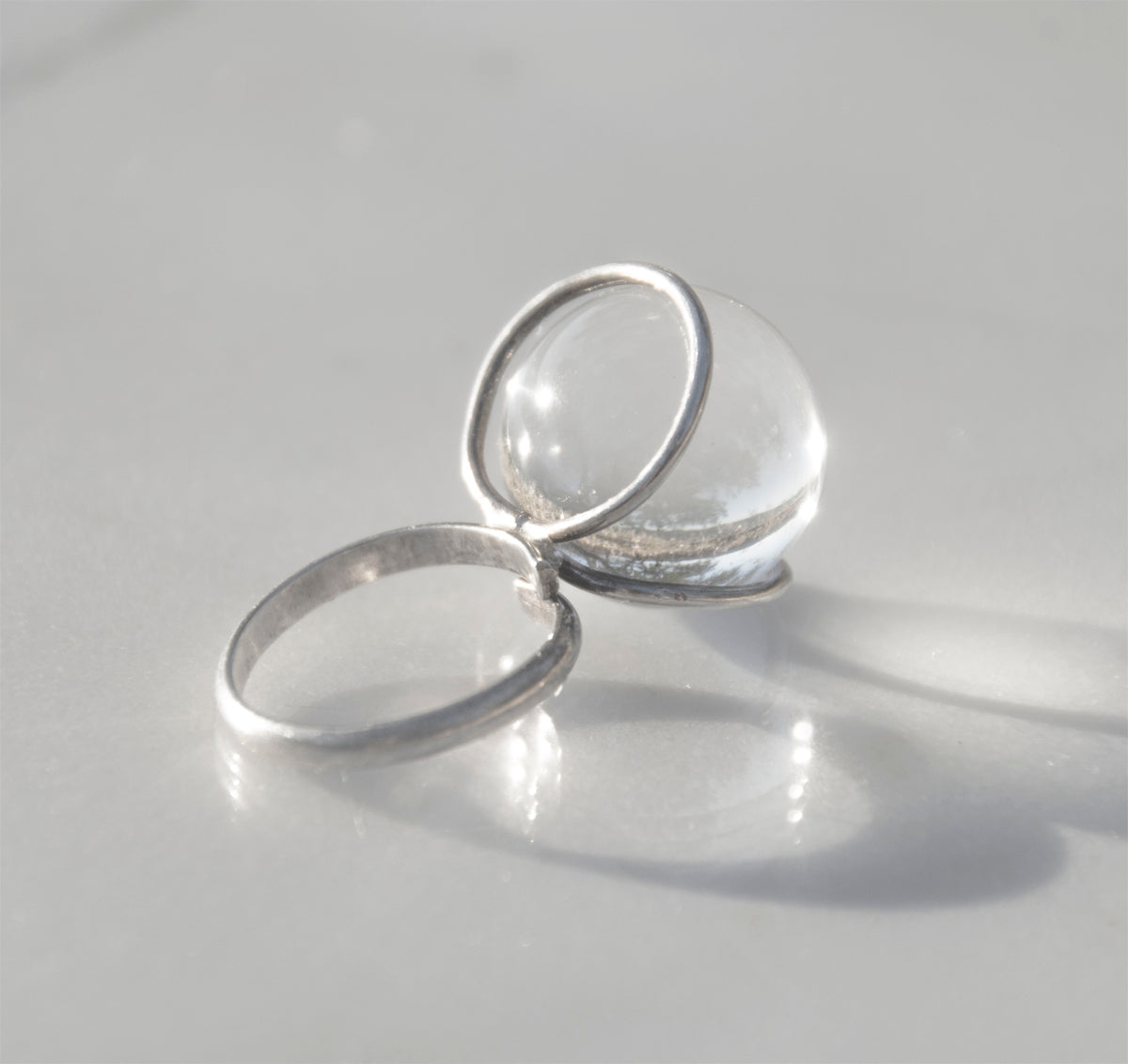 1970s Modernist Pools of Light Ring set in sterling silver with a large glass crystal ball at top. Sizing adjustable.