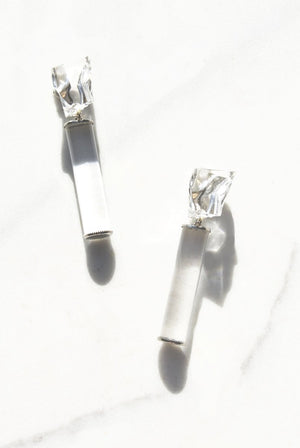 A sculptural clear lucite tube capped with sterling silver dangles off a lucite ice cube. Clip on backing or push backing available upon request.