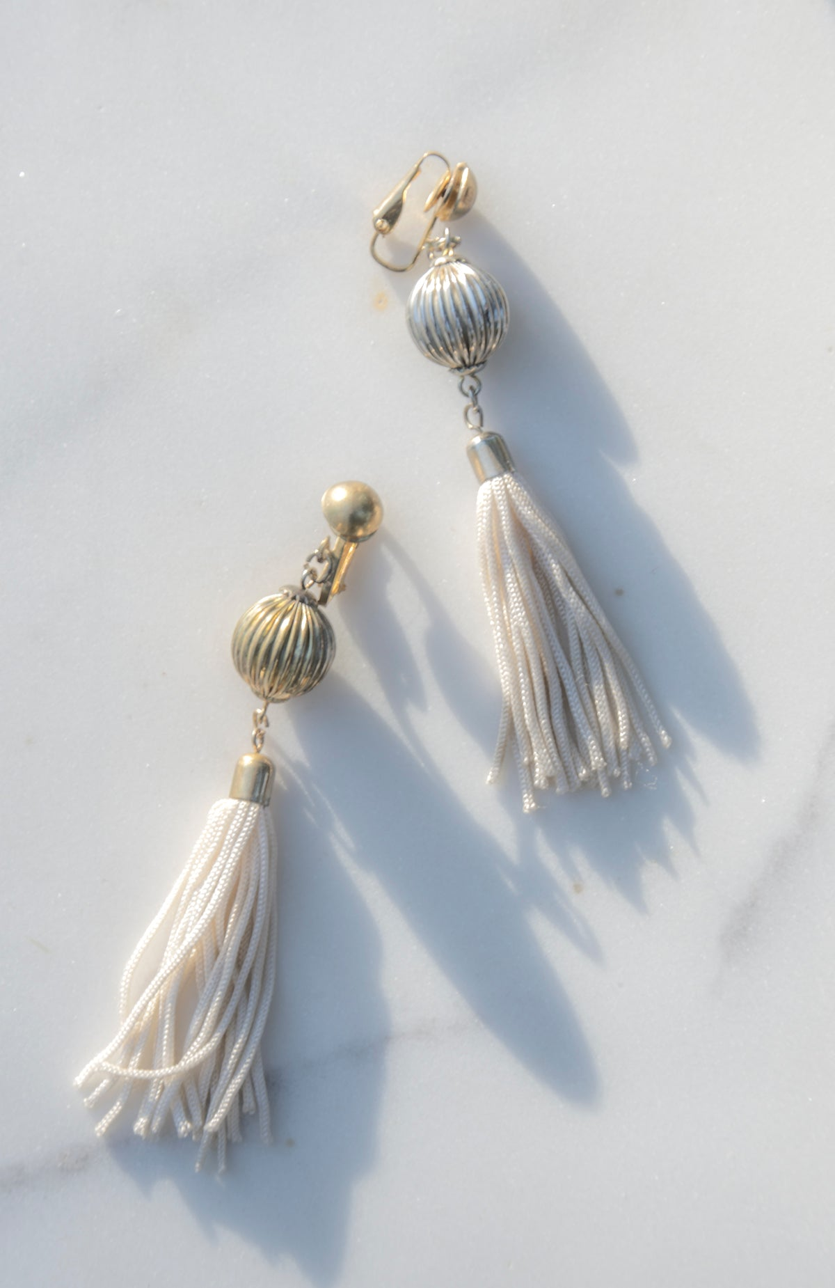 Creme Blanc Tassel Earrings from the 1980s. A round post in silver and golddrops into a cream silk tassel. Clip backing.