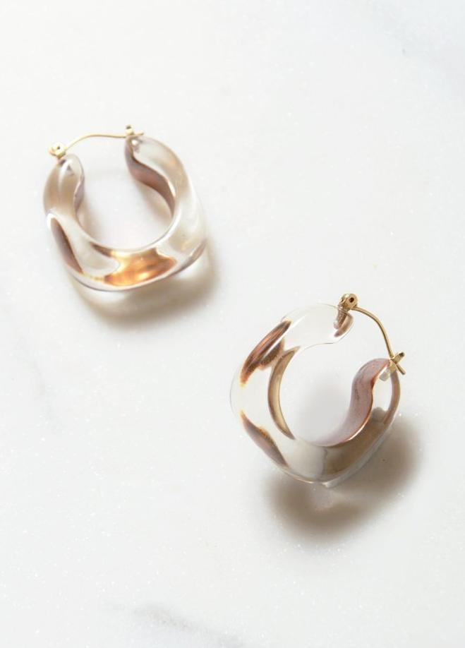 Clear lucite hoop earrings with gold inclusion detailed luxuriously with 14k gold push backing for pierced ears.