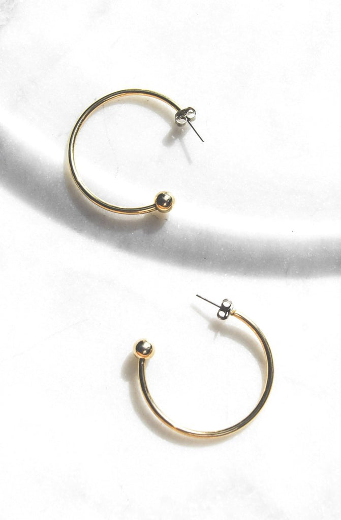 A curved gold metal hoop earrings ends in a sphere. Hypoallergenic push backing for pierced ears.