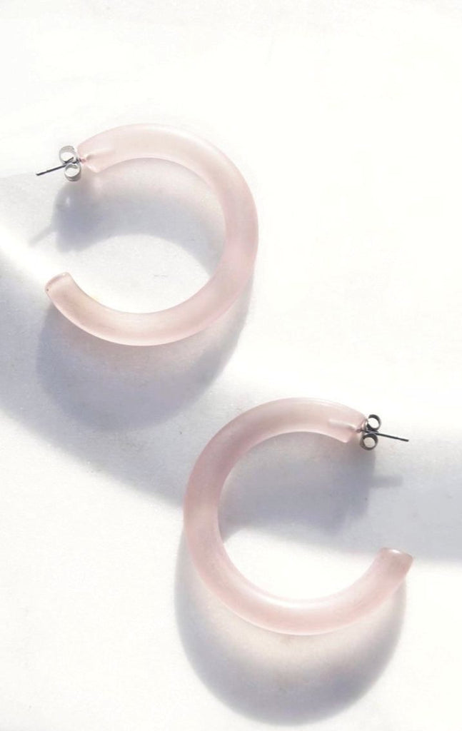 The Mayfair Hoop Earrings in pink lucite. Super lightweight 2 inch hoops perfect for sitting poolside.