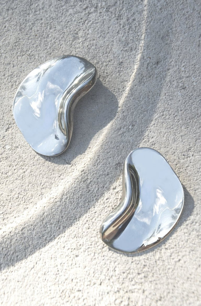 A reflective, sculptural take on the shape of the bean in the style of Elsa Peretti from the late 1970s. A sleek, modernist estate pair of earrings in silver with clip on backing.