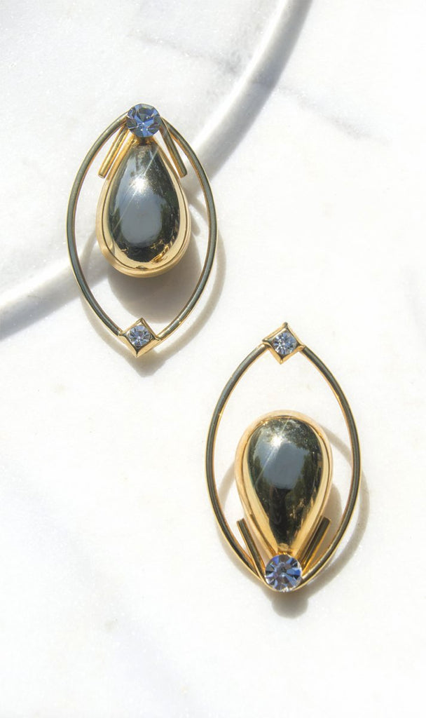 1980s estate sourced lightweight gold metal and rhinestone detailed oversized earrings, the Shalimar earrings are one of our favorite for evening.   Oval structured pieces with a sculptural egg shape within detailed with one rounded rhinestone at top and one square pave set rhinestone at bottom. Clip on backing.  Diameter : 2.25 x 1.25 inches