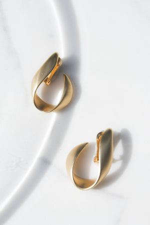 "The Flame Earrings c.1980s. Matte Gold sculptural take on the hoop in a linear 2-D form.  Clip on backing. In flawless condition.   Diameter : 2"" x 1.25"""