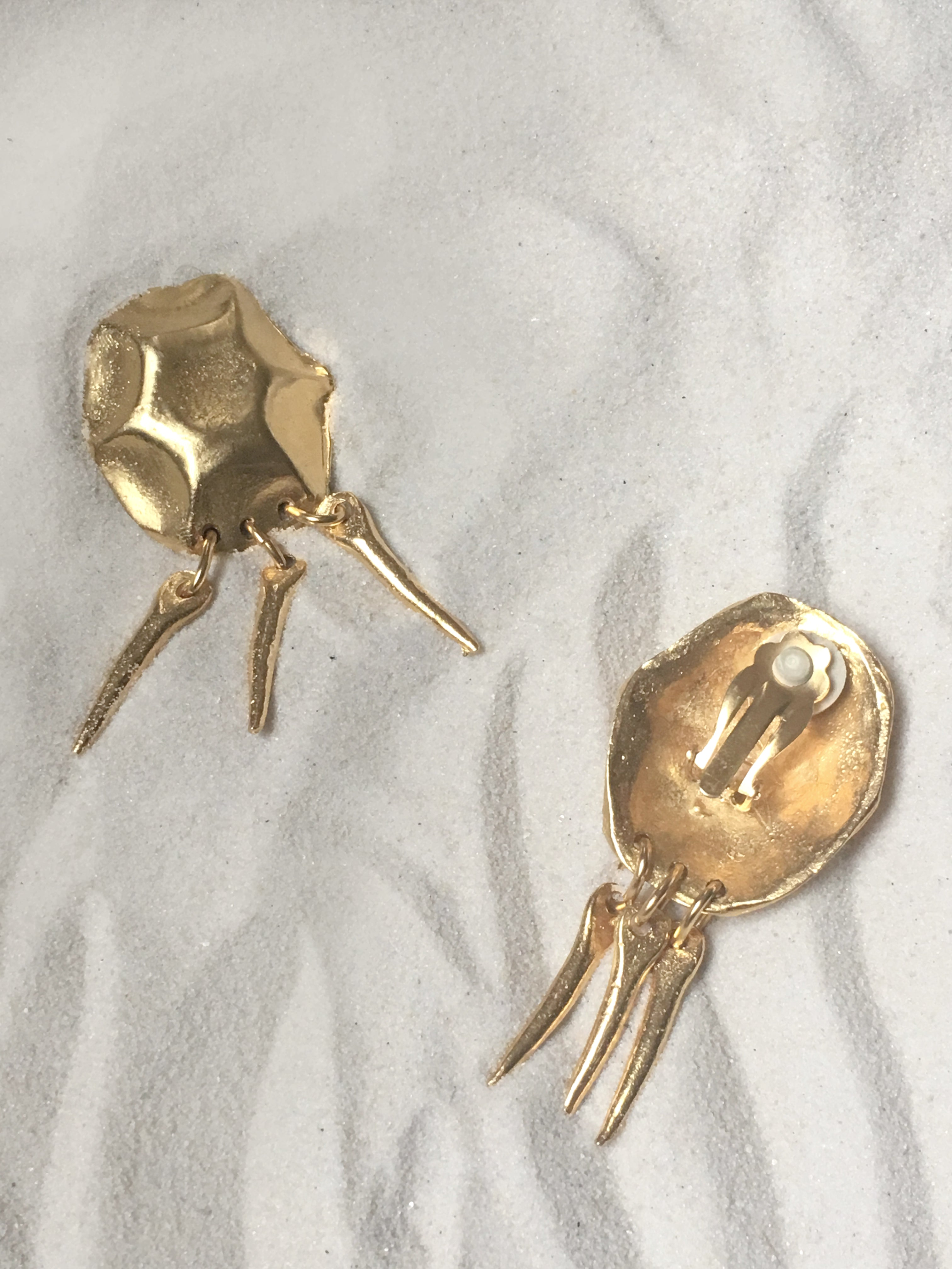 Brilliant gold coated metal earrings from the mid 1980s. A modern take on antiquity- a molded, creased oval holds three dangling tooth spikes held with oval rings. Clip on backing.