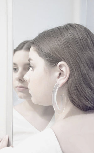 Large elongated oval hoop earrings in lucite with hypoallergenic push backing for pierced ears.