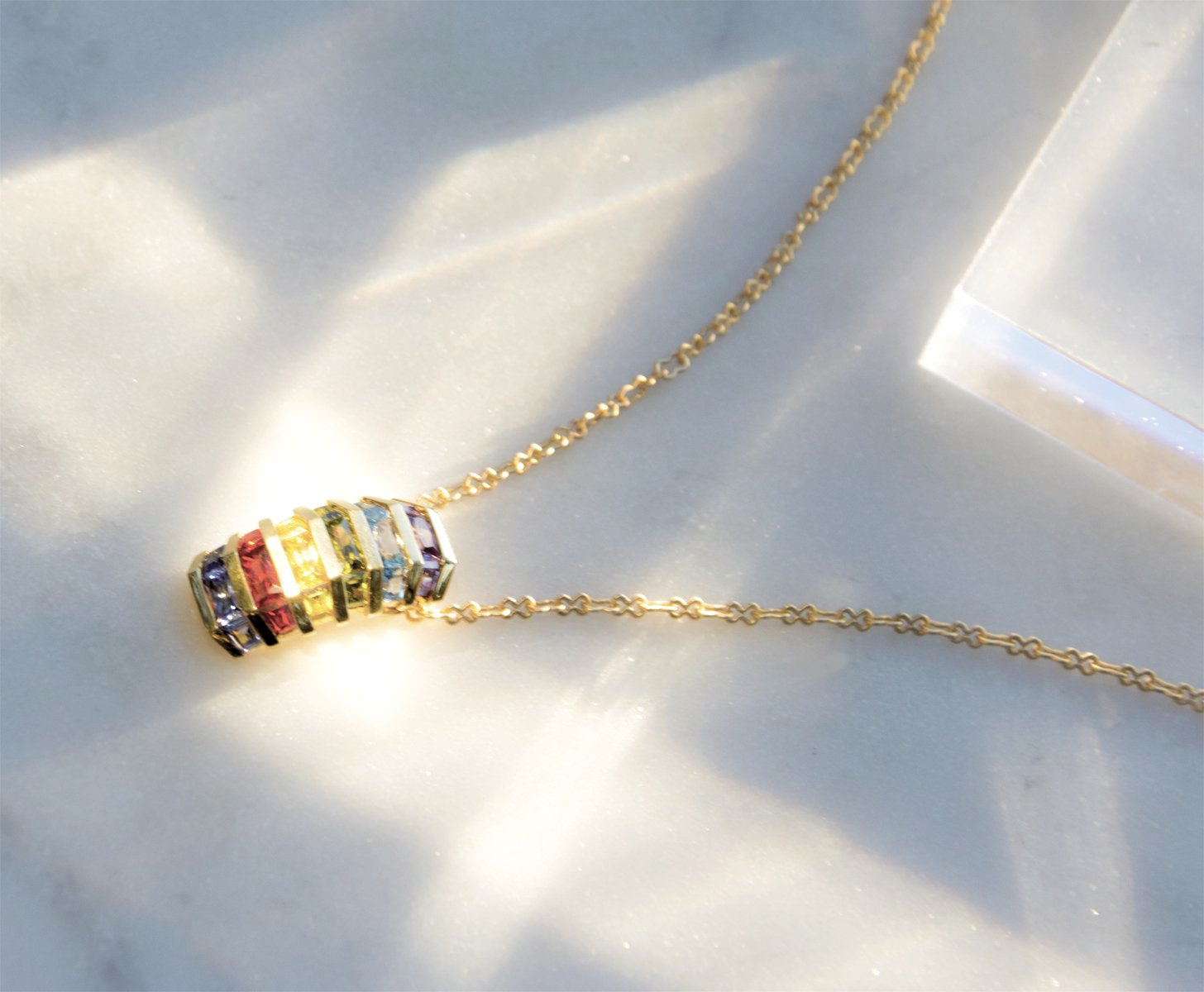 14k gold pendant necklace with a vertical array of Iolite, Amber, Citrine, Peridot, Blue Topaz, and Amethyst. Made to order, please allow 2-3 weeks for delivery.   Dimensions / length 22mm / width 12 mm inches