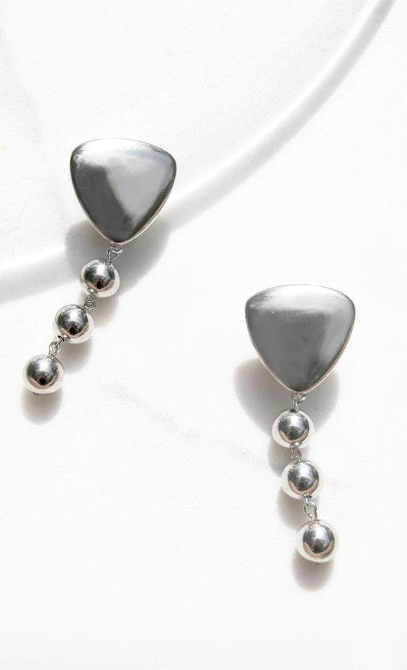 A triangular raised, 3-D shape holds a large chain of balls. Push backing for pierced ears. Lightweight.  Dimensions: 2.75 x 1.25 inches