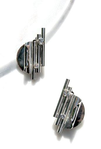 Art Deco machine age inspired 80s statement earrings in silvertone metal highlighted by a single large rhinestone.