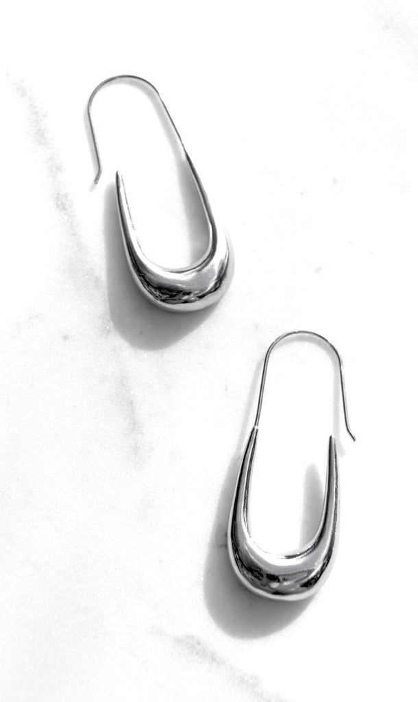 A sculptural elongated oval hoop in a two inch drop for pierced ears.