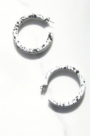 Large white coated hollow metal hoop earrings inspired by CBGB era Blondie and her collaborations with designer Stephen Sprouse.  Detailed with black paint splatter throughout. Hypoallergenic push backing for pierced ears.
