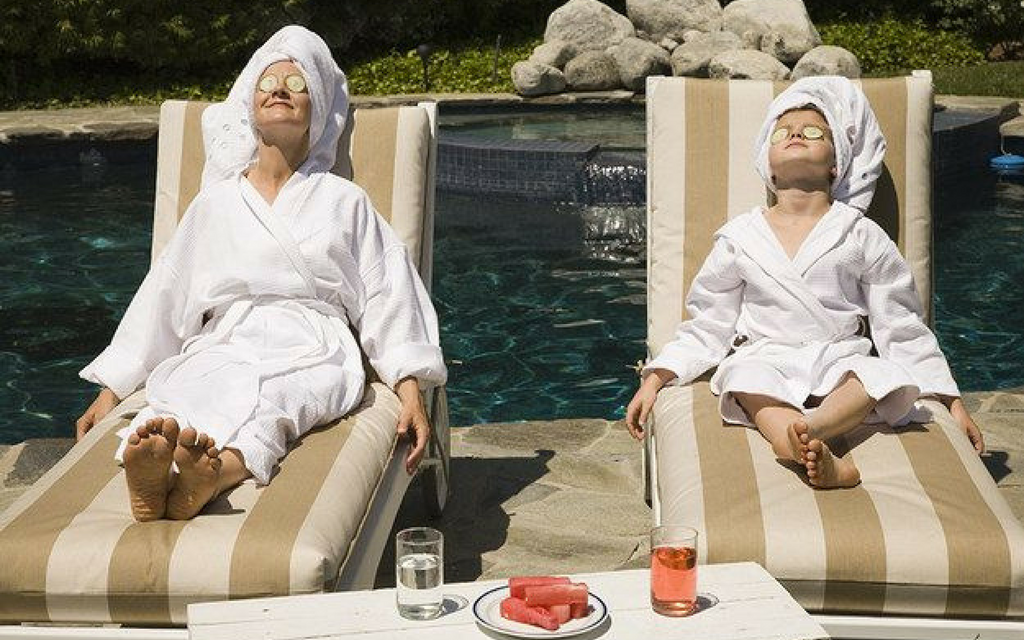 mom and daughter wearing robes and laying on pool chairs