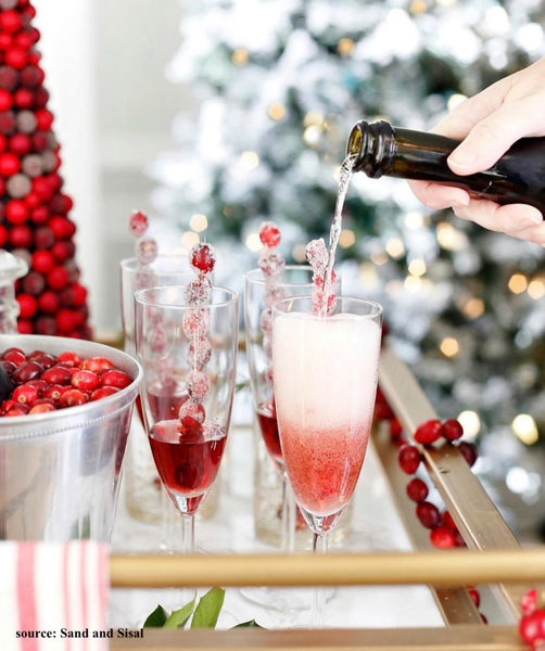 cranberry spritzer cocktails in champagne flutes with sugared cranberry sticks