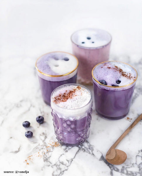 blueberry lattes in glass cups on marble countertop