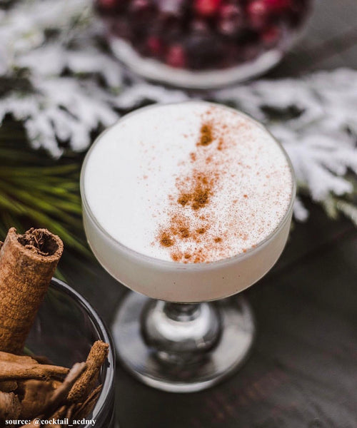 festive holiday eggnog cocktail in glass with cinnamon sticks
