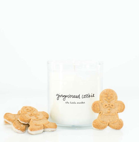 white candle with gingerbread men cookies