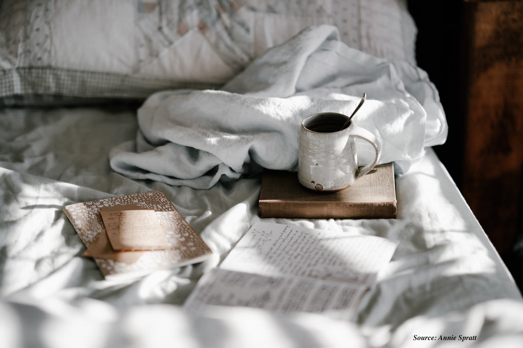 Journal on a bed with coffee and books