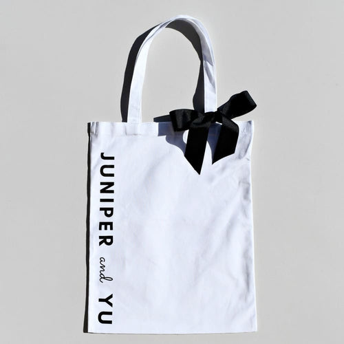 white cotton tote bag with black bow ribbon