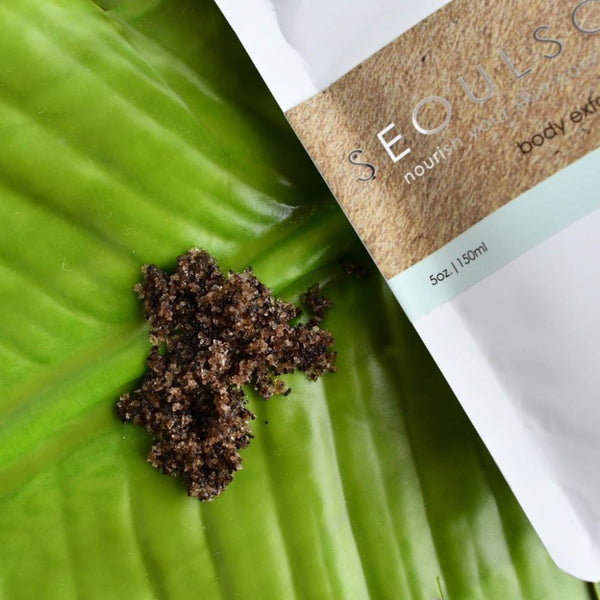 Peppermint coffee body scrub grains on a palm leaf
