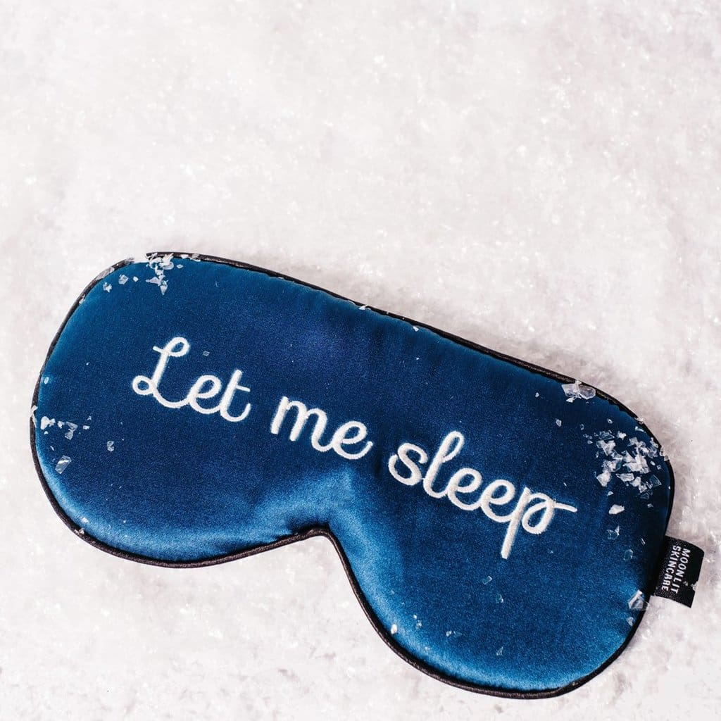 "Satin navy sleep eye mask with the words ""Let me Sleep"" written across the front"