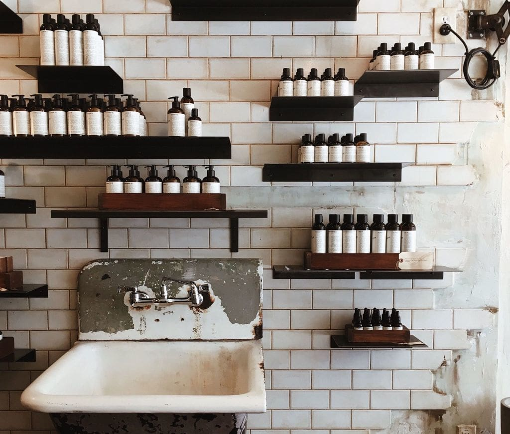 white sink and floating shelves with bottles
