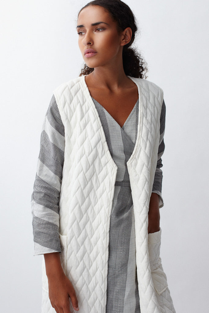 Close-up of KAI & KLO white quilted long vest.