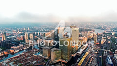 Aerial Image Photo of London City Financial District Skyscrapers in Canary Wharf Helicopter Flight View with Sunrise Skyline Around the Business Buildings UK