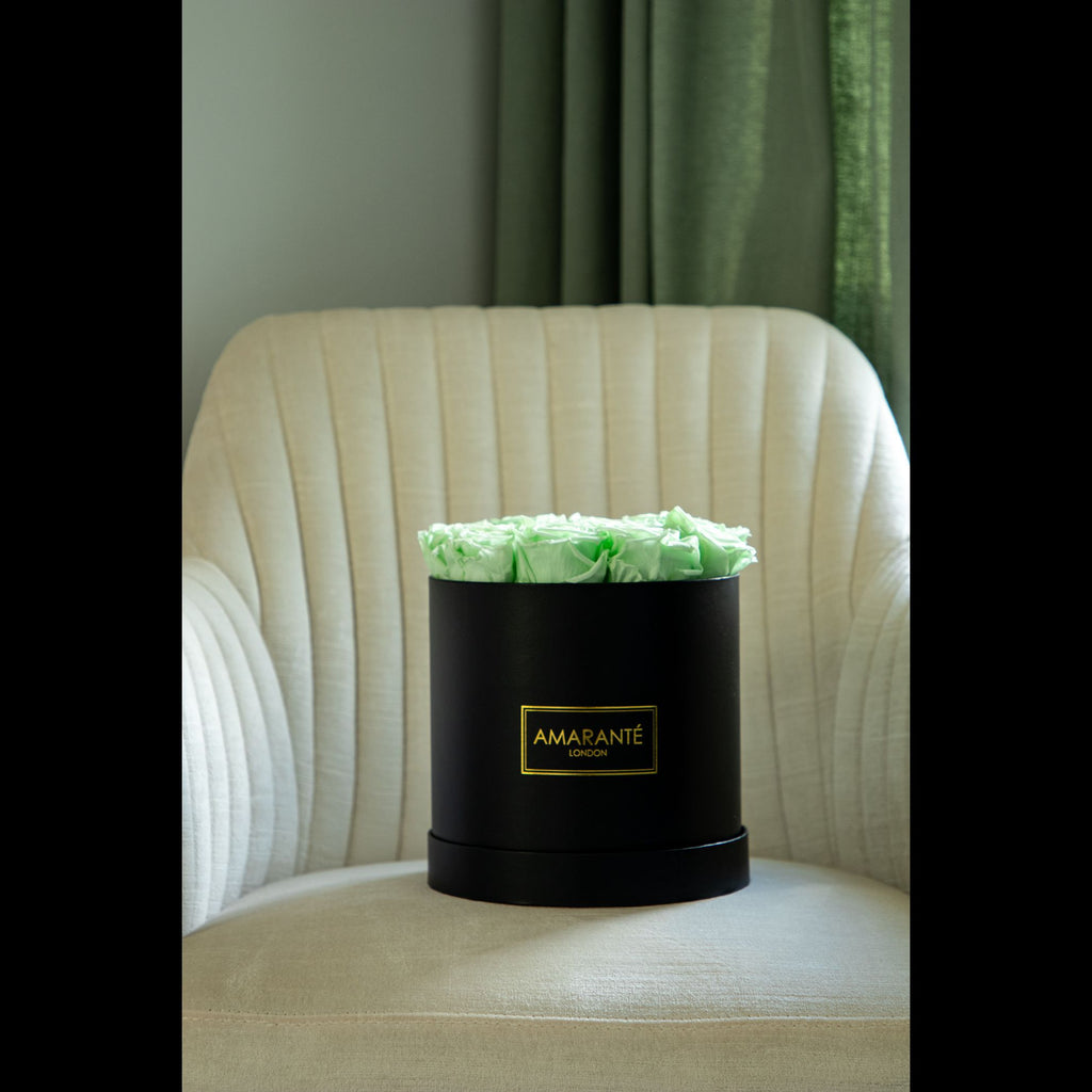 Preserved flowers in a pristine black rose box presented in a stylish bedroom
