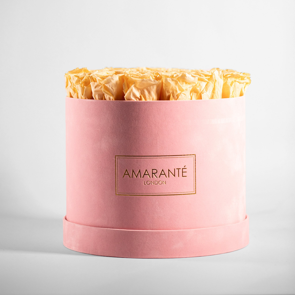 Peach coloured preserved flowers in a large pink hatbox (roses)