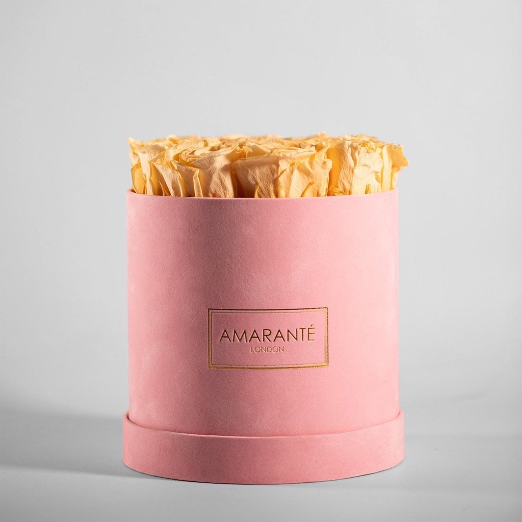 Peach coloured preserved flowers in a  pink hatbox (roses)
