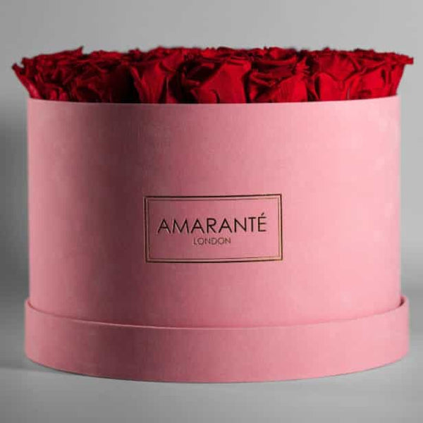 Red infinty roses in large pink suede hatbox