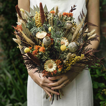 Exotic dried flowers infused with mellow orange and warm yellow stems featured in the floral collection