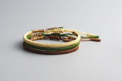Yellow, green and brown stack of tibetan handmade bracelets.