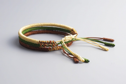 A stack of three bracelets (yellow, green, and brown).