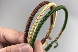 Person holding a brown, yellow, and green bracelet.
