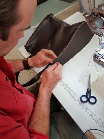 Angus hand stitching the corners of the Giovanni Tote Bags for added strength.