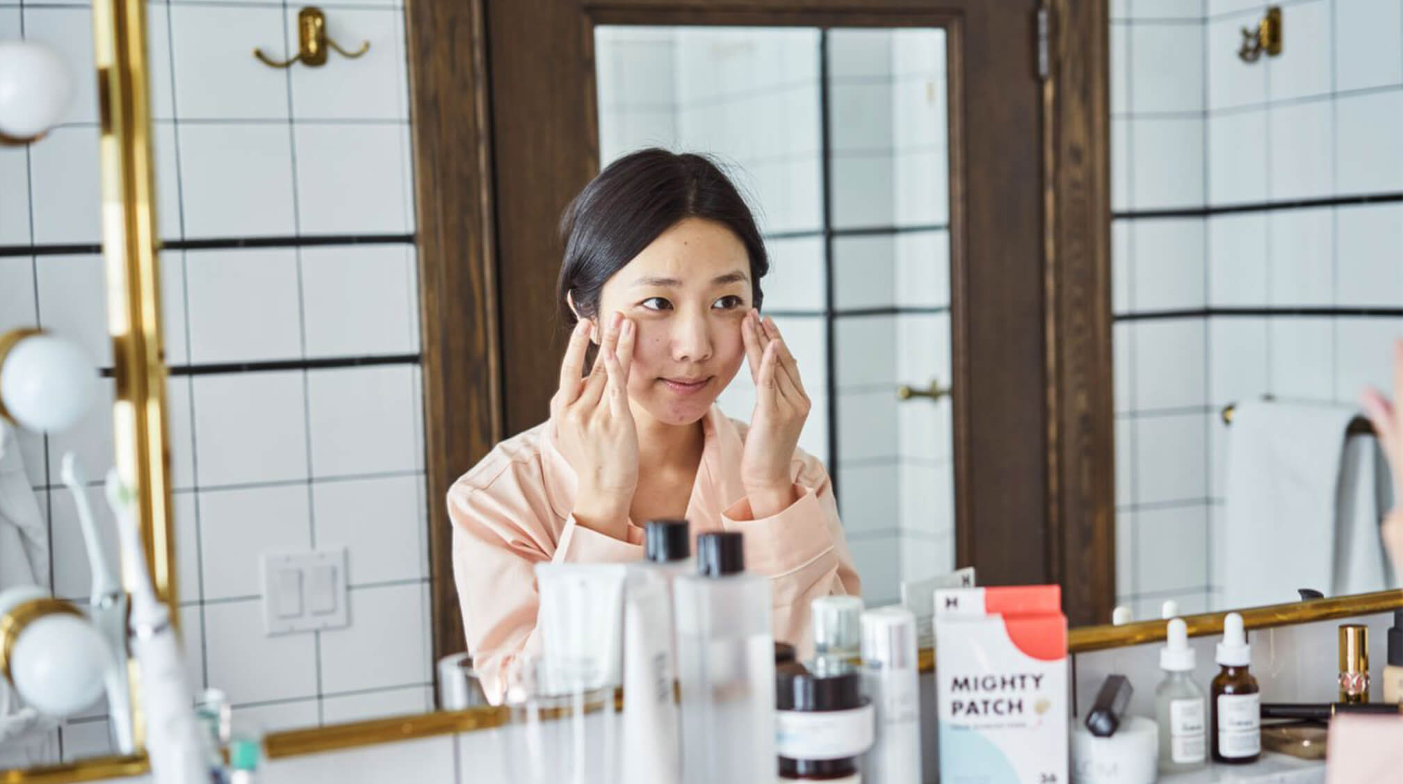 Asian woman applying skincare to face