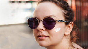 woman in sunglasses and with sunscreen on face