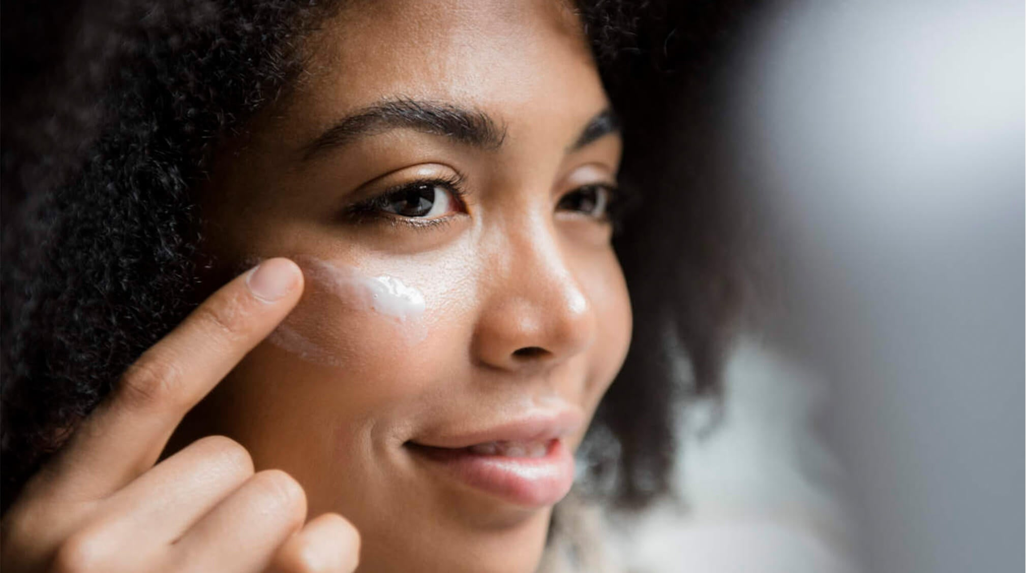 african american woman applying moisturizer on face