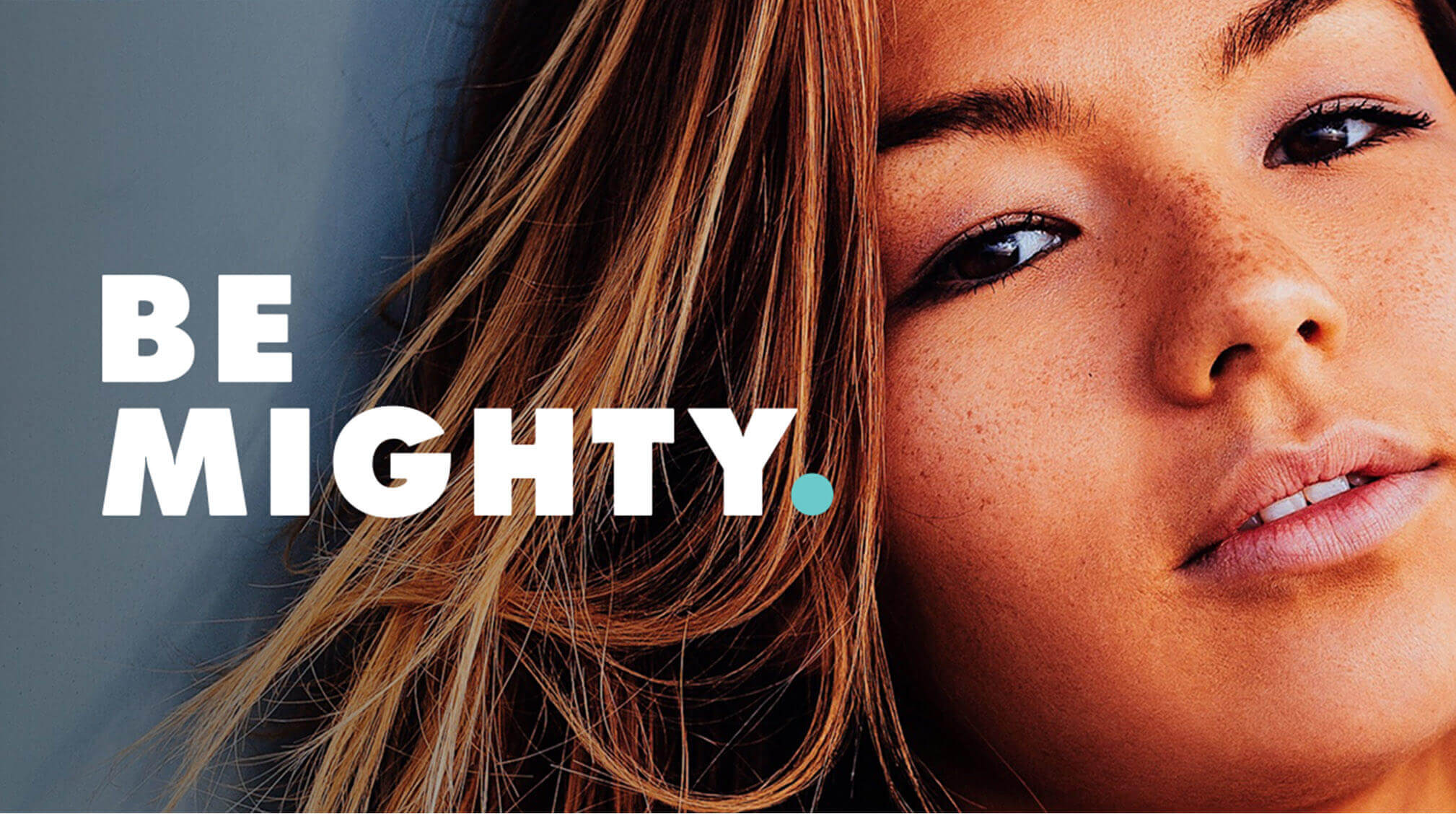 "face of woman next to text reading ""be mighty"""