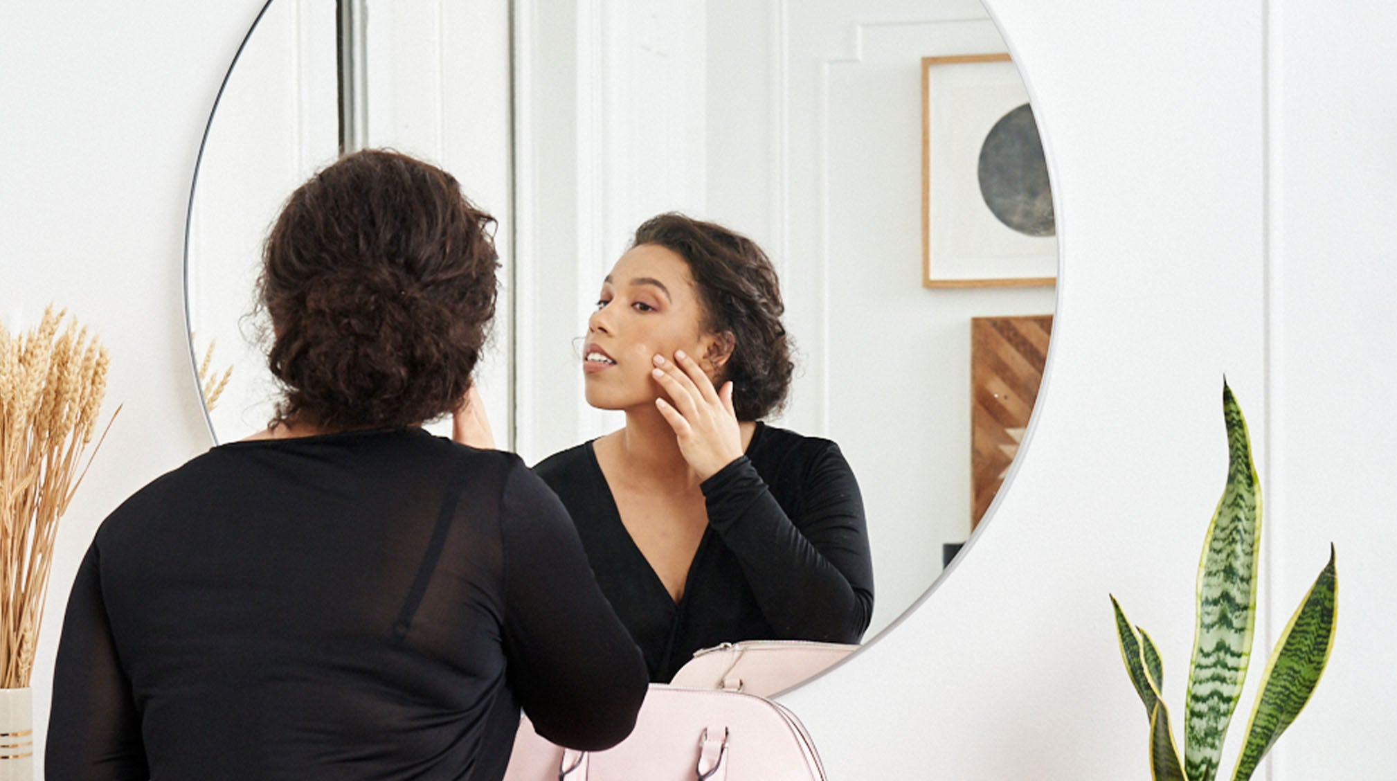 Working woman checking out skin in front of mirror