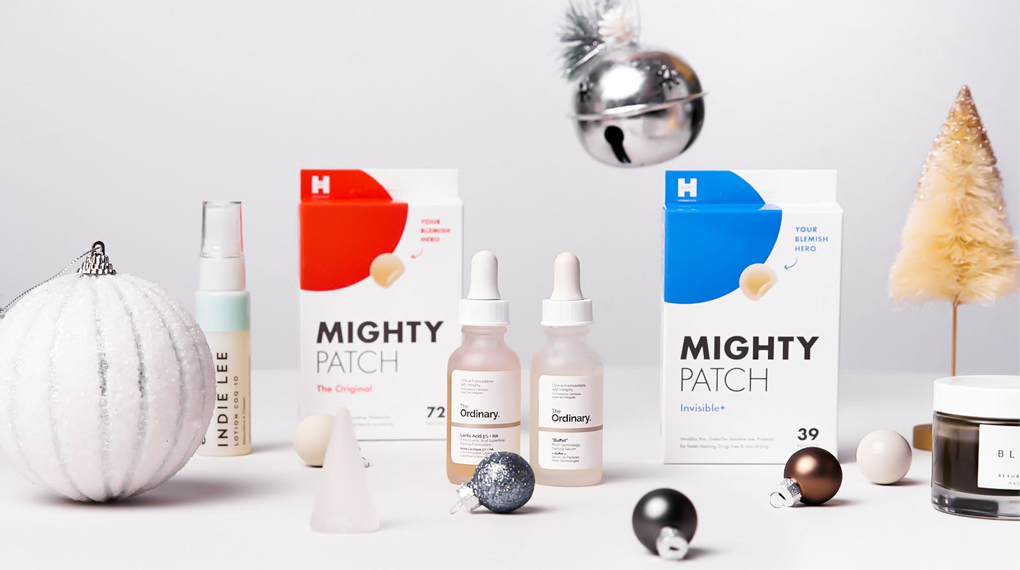 Acne care gifts from Hero Cosmetics, The Ordinary, Indie Lee and Herbivore next to Christmas ornaments