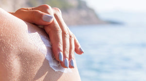 hands applying sunscreen to shoulders
