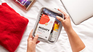 Hand holding travel skincare bag with Mighty Patch Original