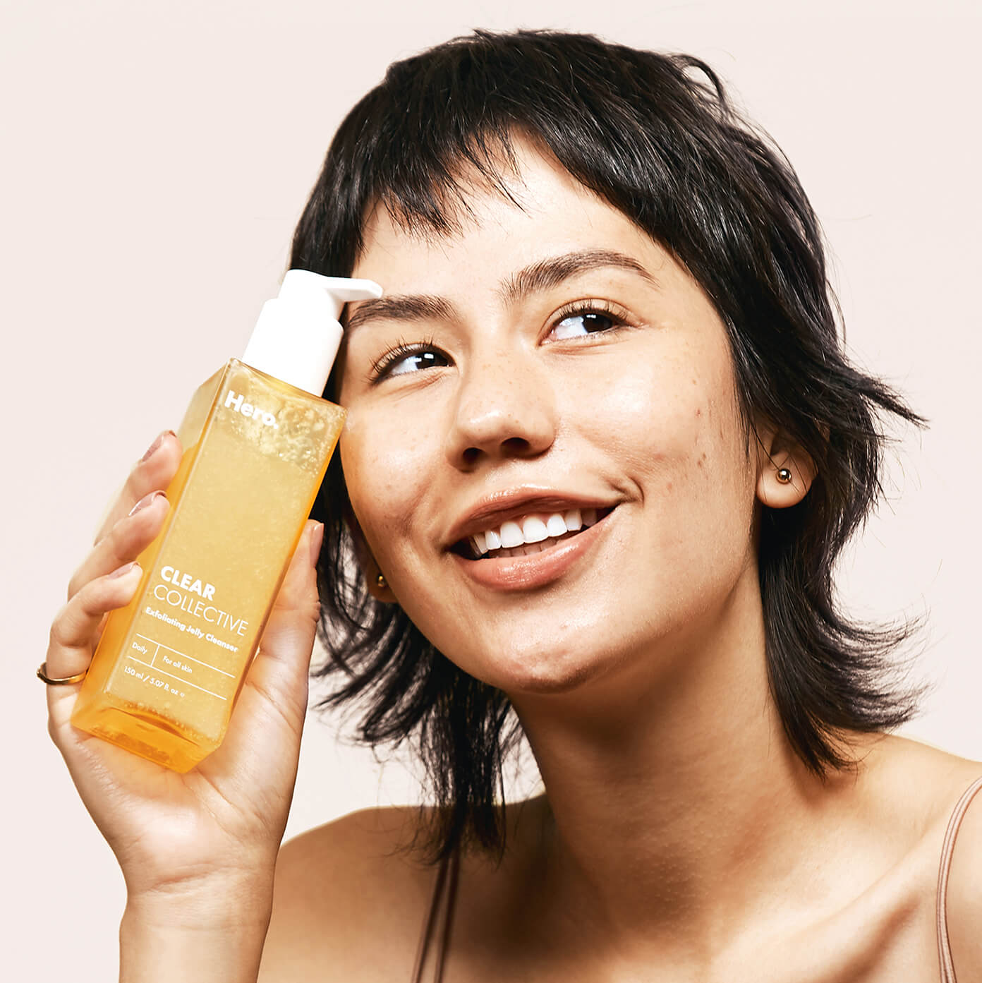 Model holding Clear Collective Exfoliating Jelly Cleanser